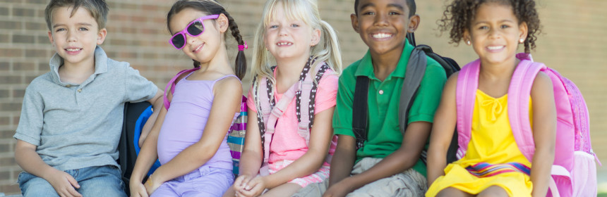 Diverse group of elementary students playing outside